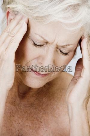 a senior woman with a headache