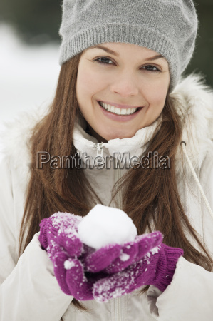 a young woman holding a snowball