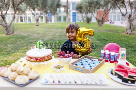 little boy with golden balloon behind