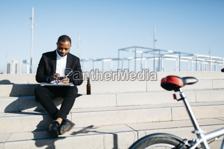 businessman sitting on stairs with bottle