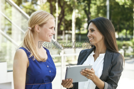 two smiling women with digital tablet