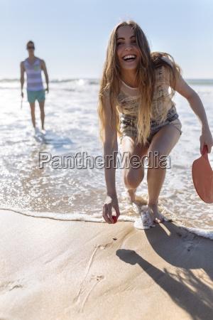 laughing teenage girl playing beach paddles