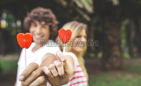 young couple holding heart shaped lollipops