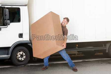 delivery man carrying heavy box