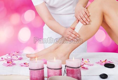beautician waxing woman leg with wax