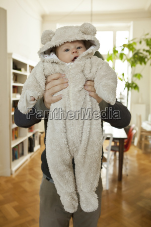 baby in bear costume being held