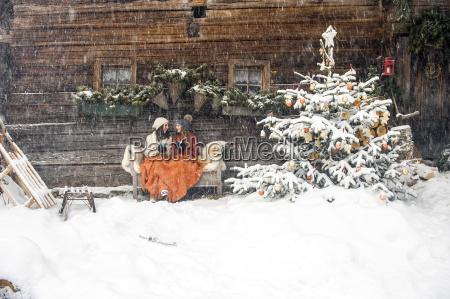 freunde auf der bank von weihnachtsbaum