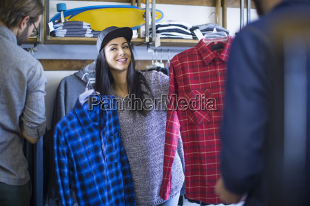 friends choosing clothes in shop