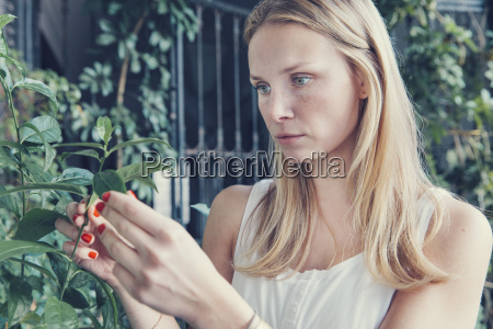 young woman looking at plants on