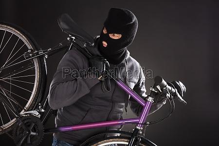 person traegt diebstahl balaclava ein fahrrad