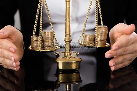 anwaltshandschutz gerechtigkeit waage mit muenzen