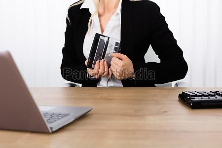 businesswoman stealing a calculator