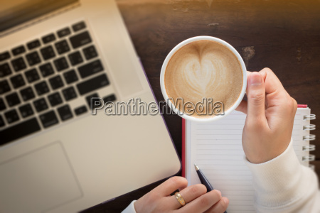 hand on cup of coffee at