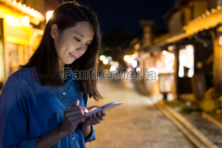 woman using cellphone at night in
