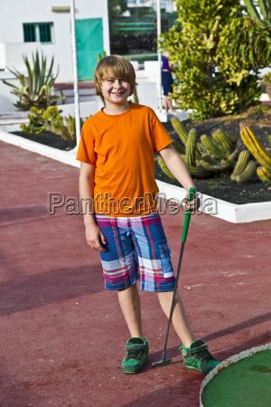 junge spielt minigolf auf dem platz