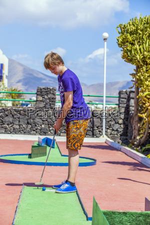 junge liebt mini golf zu spielen