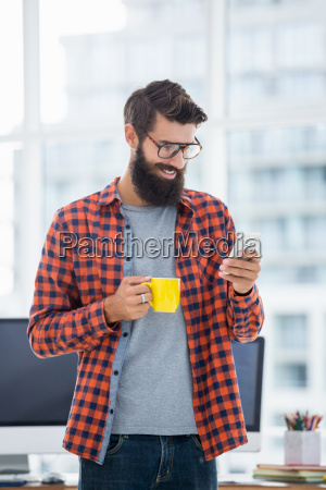 hipster using smartphone and drinking coffee