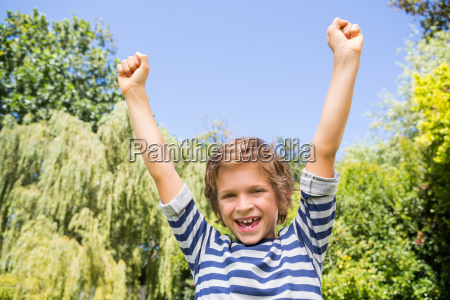 portrait of happy boy raising arms