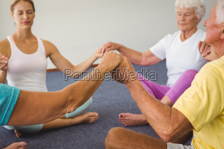 concentrated seniors holding hands together in