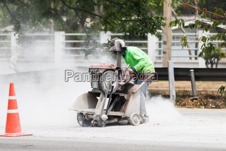 worker cutting asphalt road