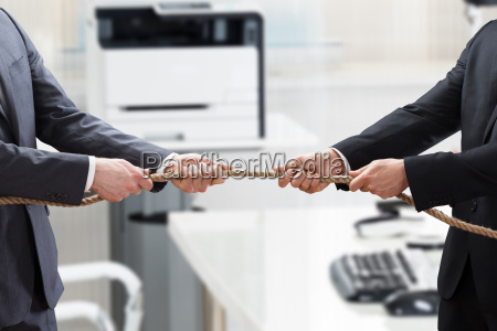 two businesspeople playing tug of war