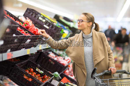 pretty young woman buying groceries in