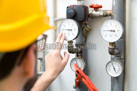 maintenance technician checking pressure meters