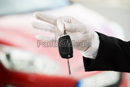 valet boy hand holding car key