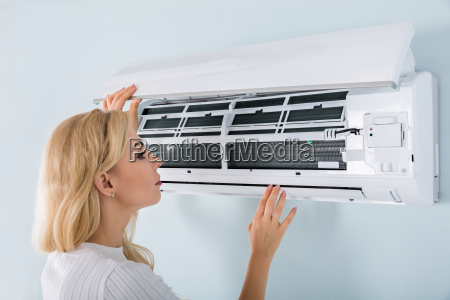 young woman checking air conditioner