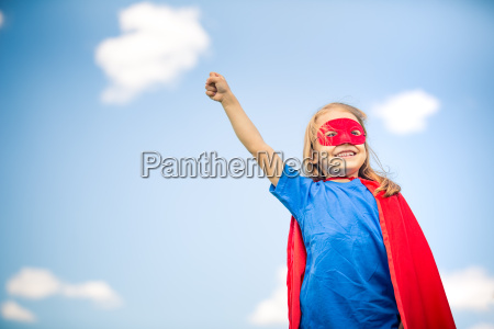 lustige kleine maedchen macht superheld plaing