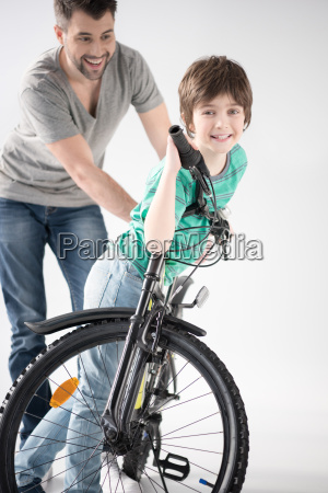 cheerful father teaching son how to