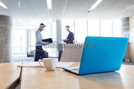 laptop und kaffeetasse auf konferenztisch mit