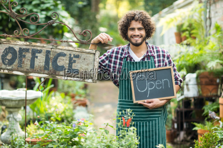 male gardener holding open sign by