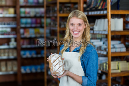 smiling female staff holding bread in