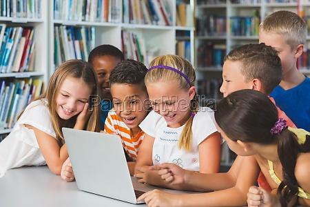 laechelnde schulkinder die laptop in der