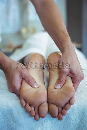 physiotherapeut der einer frau fussmassage gibt