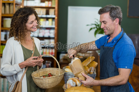 smiling woman purchasing bread at bakery