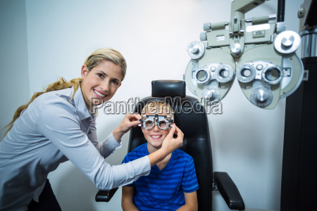 female optometrist examining young patient with