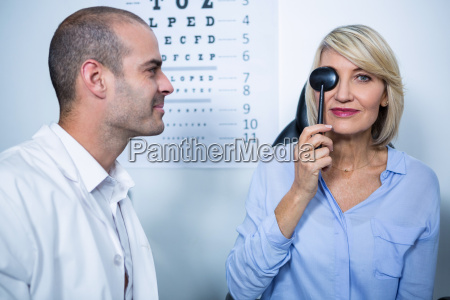 optometrist examining female patient with medical