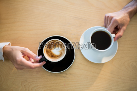 hands of couple holding cup of