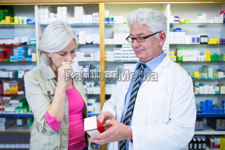 apotheker der dem kunden medizin zeigt