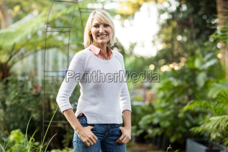 confident mature woman standing at greenhouse