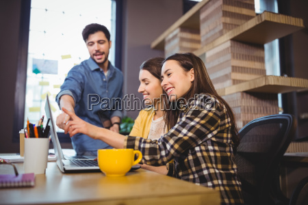 coworkers smiling while pointing at laptop