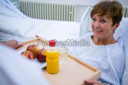 nurse serving a breakfast to patient