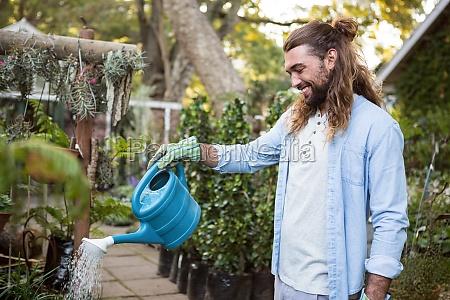 happy gardener watering plants at community