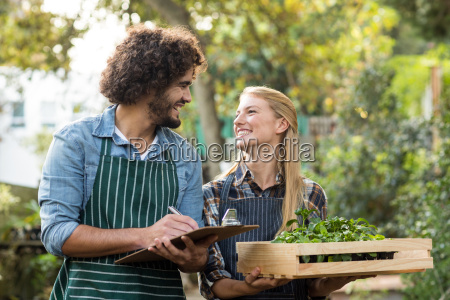 woman holding plants in crate while