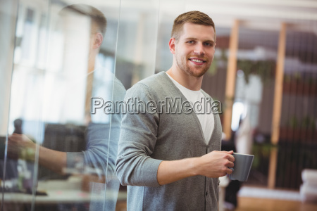 businessman holding coffee cup in office