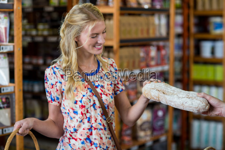 smiling woman purchasing a loaf of