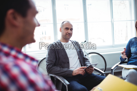 businessman looking at coworker while using