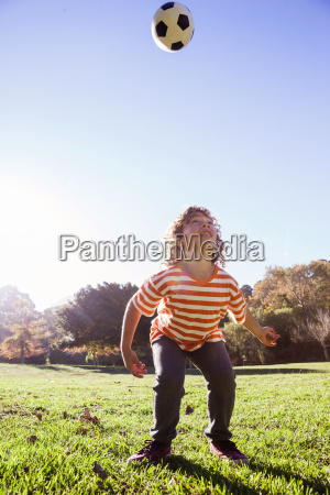 boy playing with soccer ball in